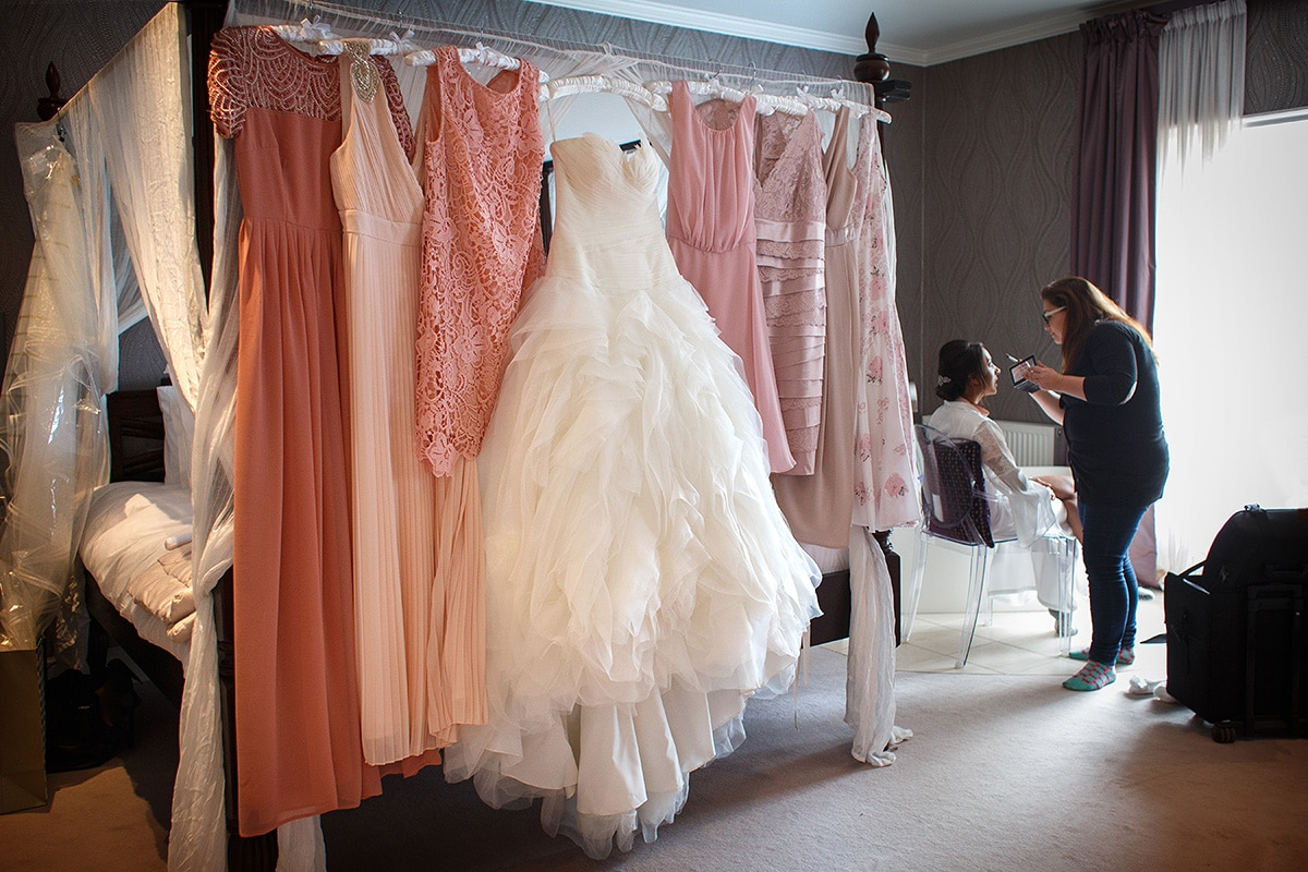the girls dresses hanging up with the bride having her makeup done in the background