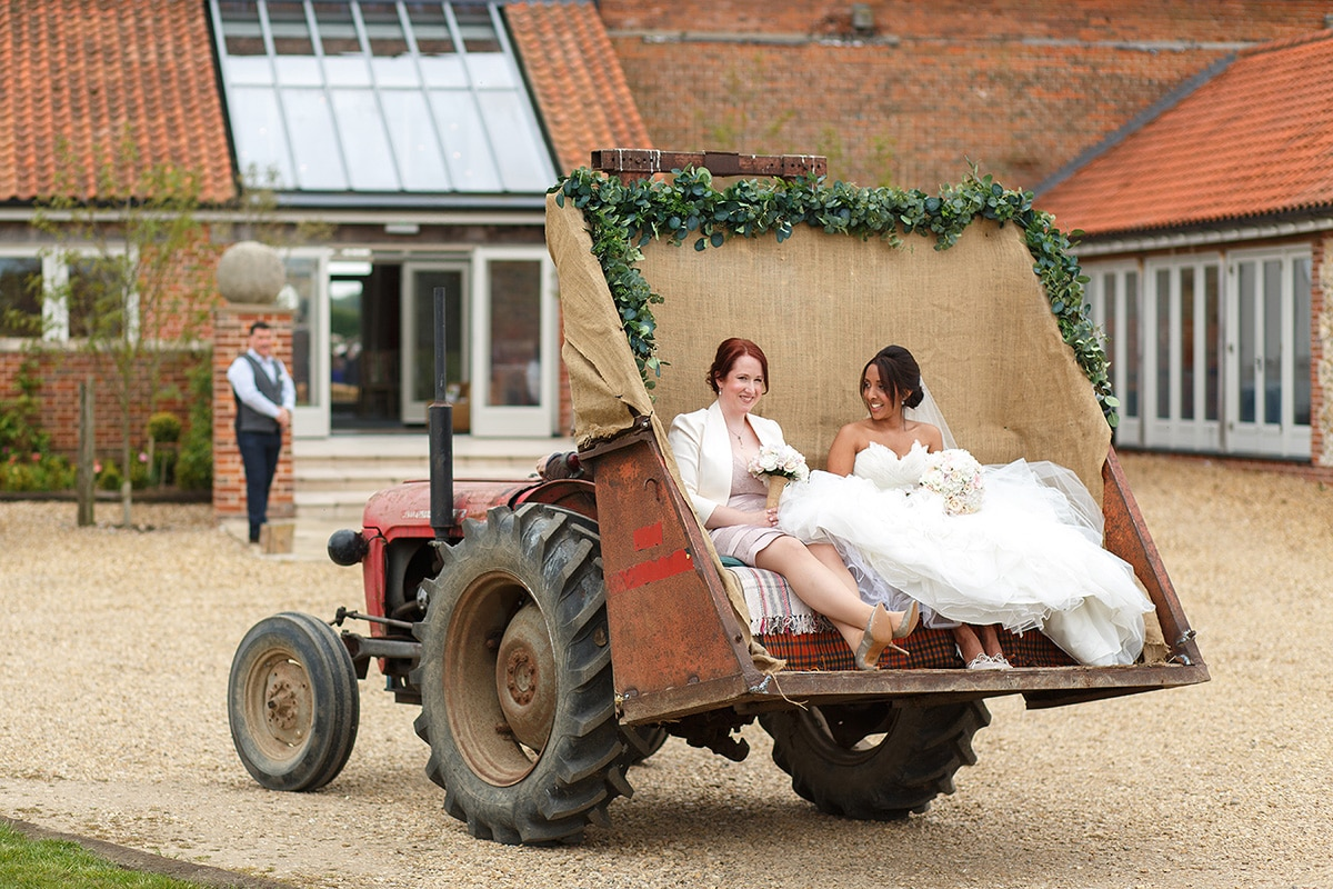 the bride and her maid of honour in the back of the tractor