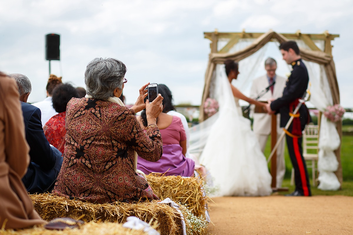 a guest takes a photo during the outdoor ceremony