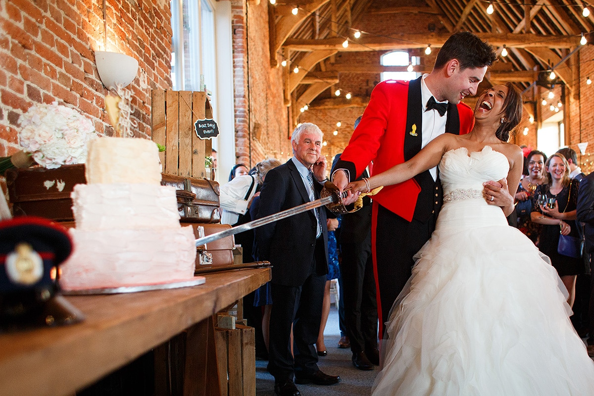 bride and groom cut the cake inside Godwick Barn
