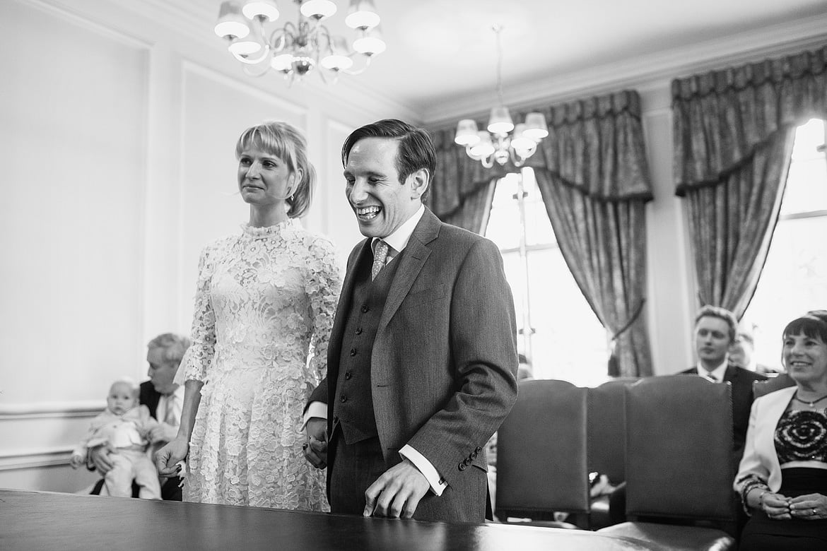bride and groom share a joke during the ceremony