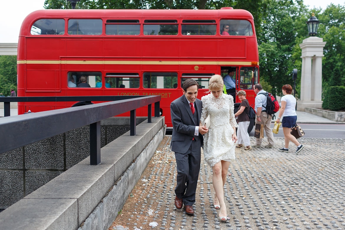 david and rowena walk through london with a routemaster bus in the background