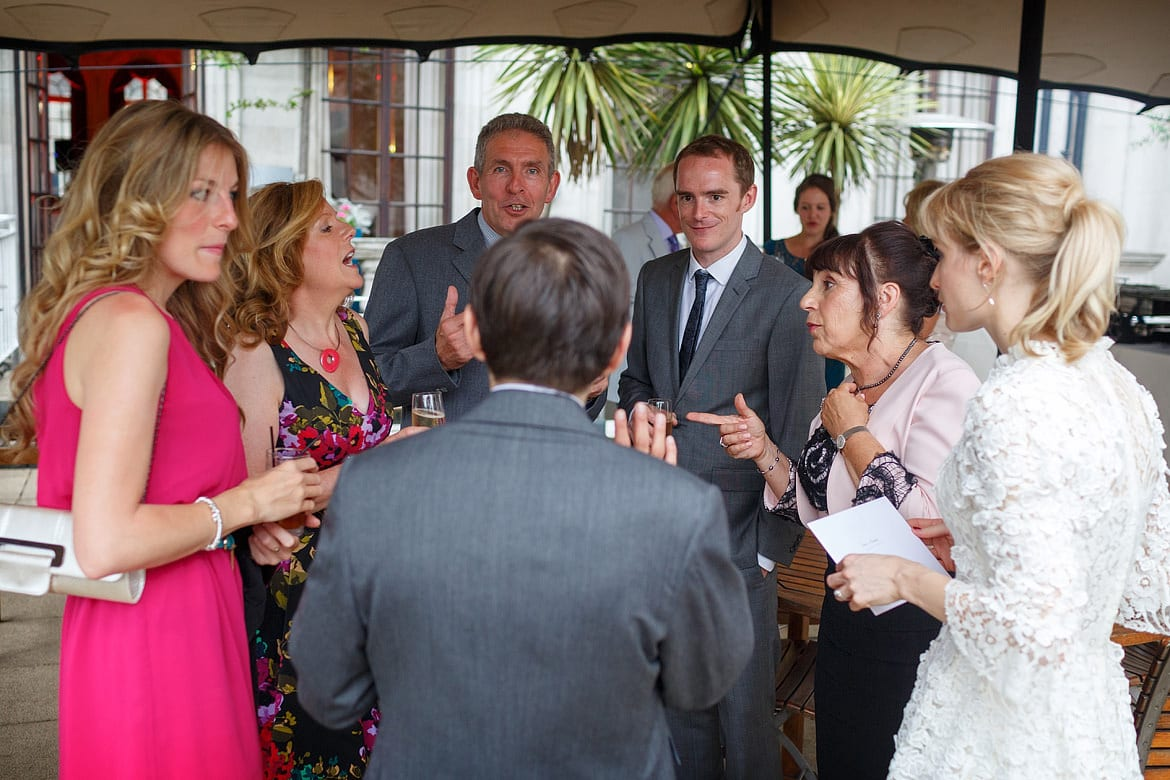the groom chats with the guests outside