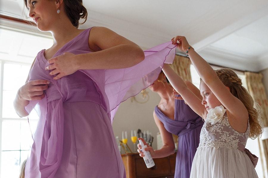 a flowergirl holds up a bridesmaids dress