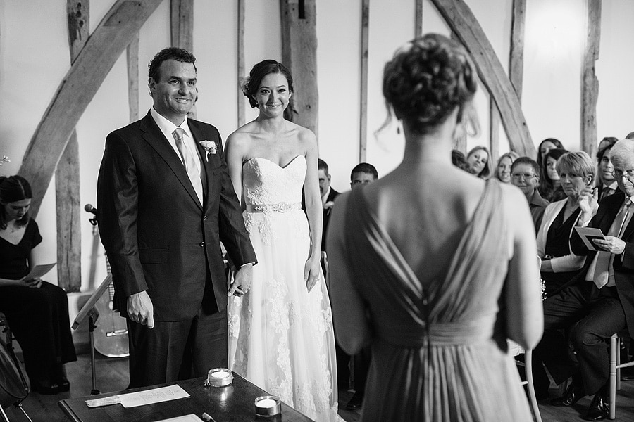 bride and groom listen to a reading
