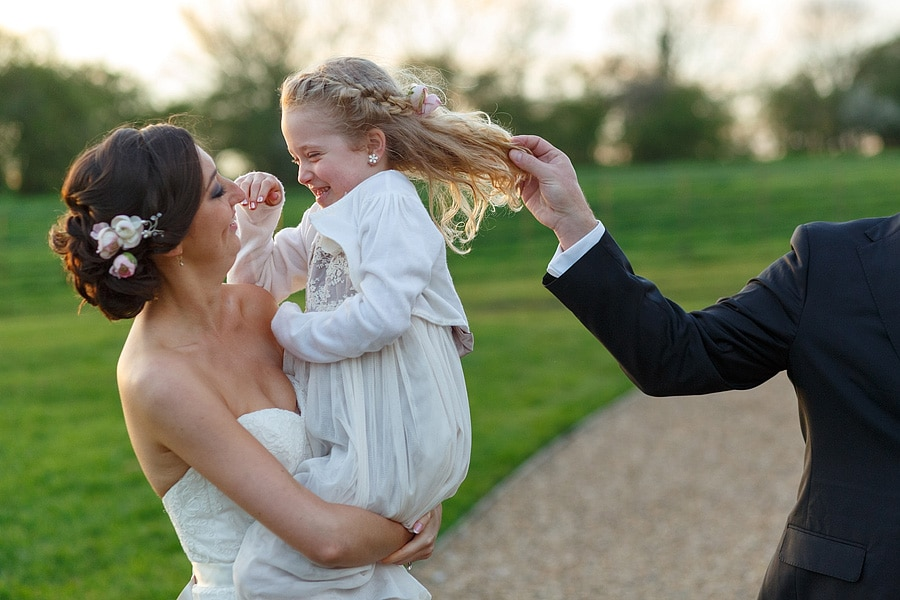 the bride holding a smiling flowergirl