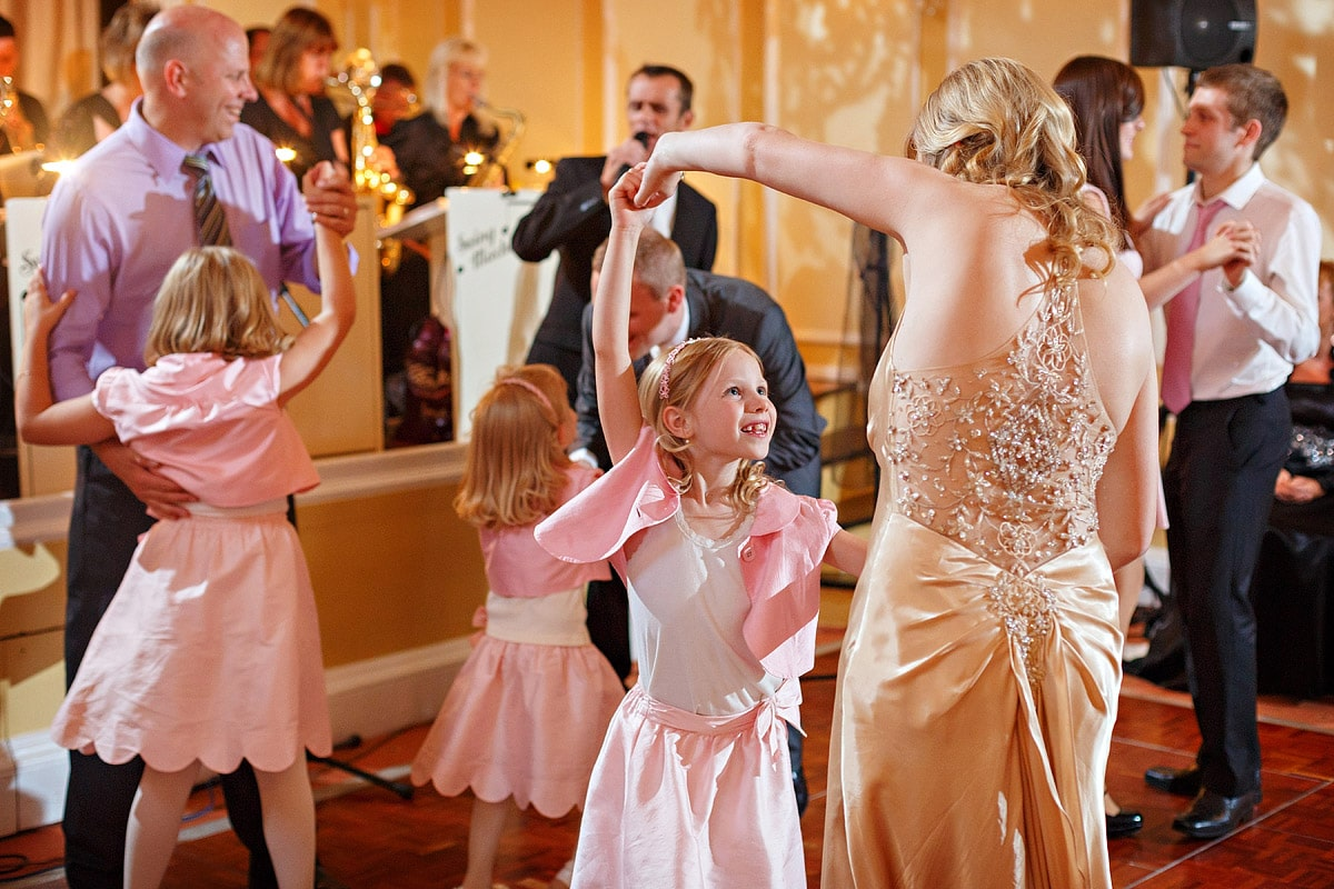a flowergirl dances with the bride
