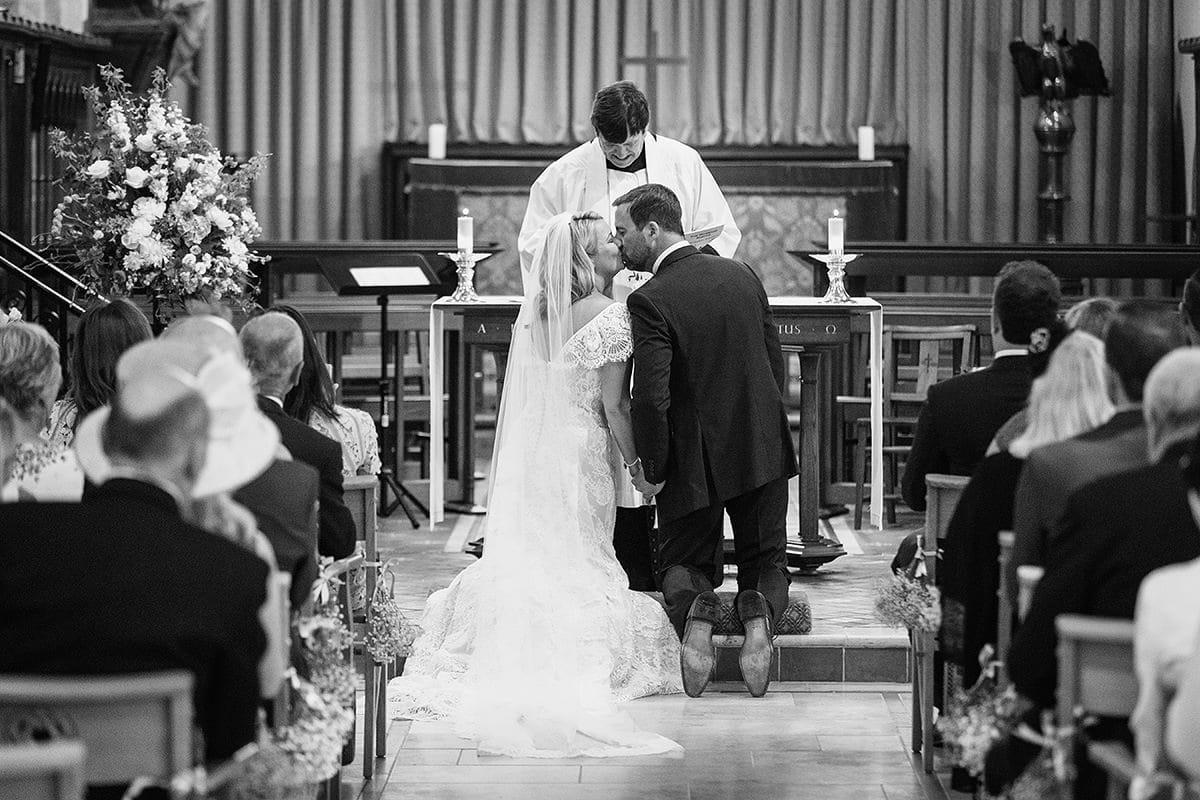 laura and todd kiss in cuckfield church