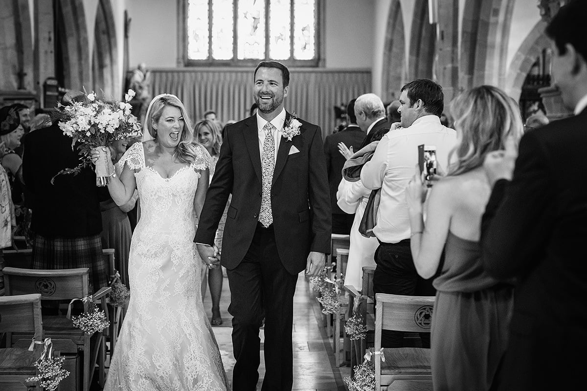 laura and todd walk down the aisle after their wedding ceremony