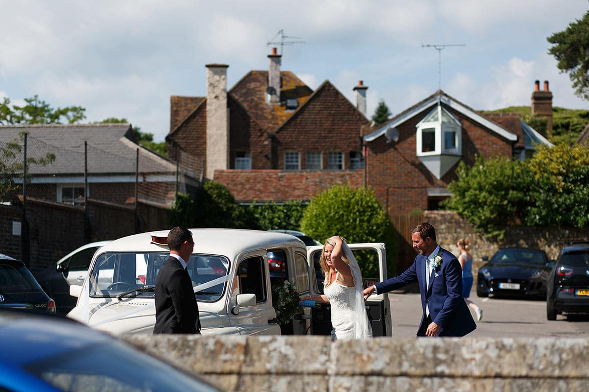 bride and groom get into their white wedding taxi