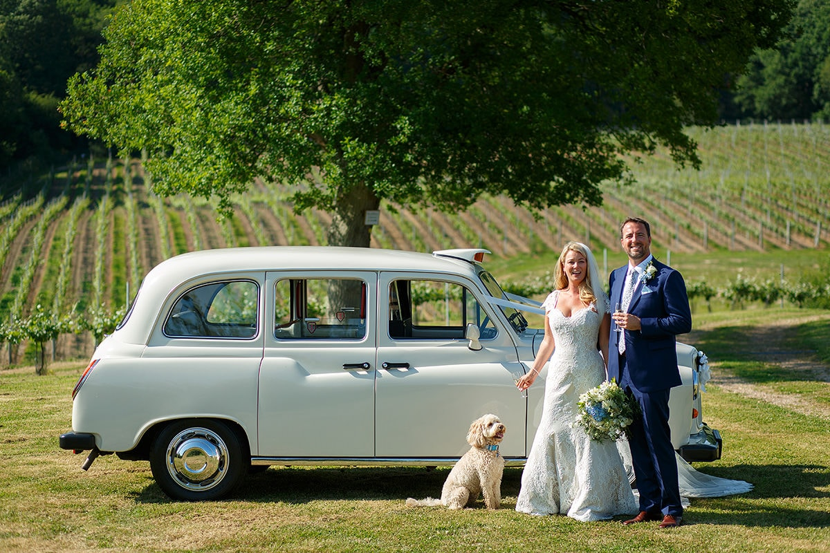 laura and todd pose with their dog and the taxi