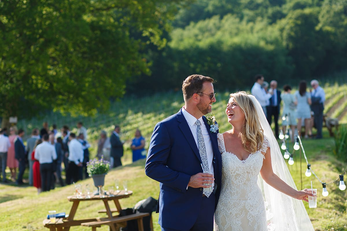 bride and groom laughing together with bluebell vineyard in the background