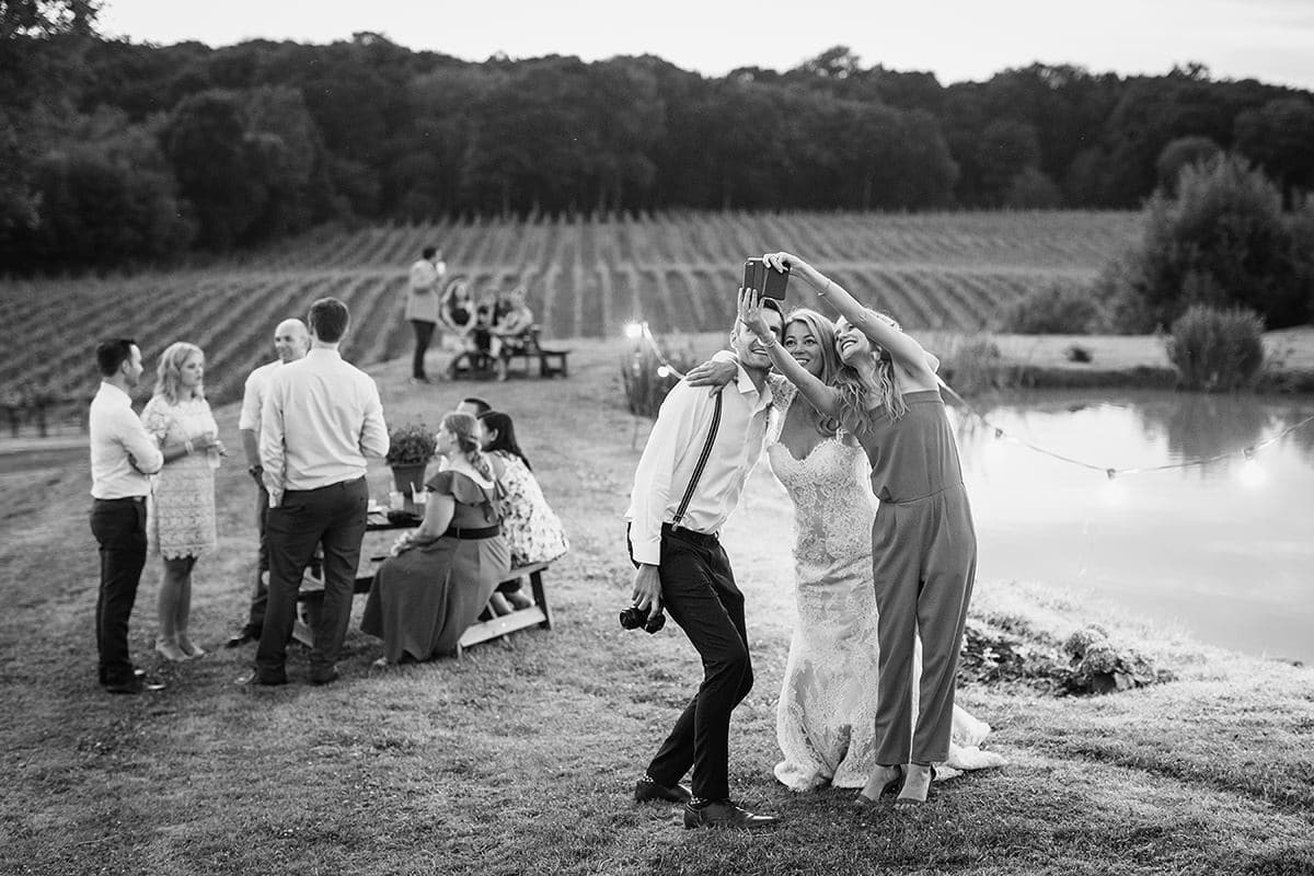 laura takes a selfie with guests with the vineyard in the background