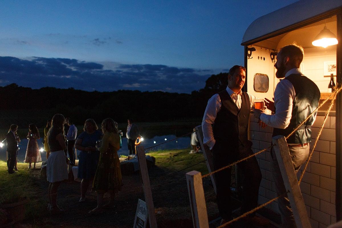wedding guests enjoy a drink as evening falls