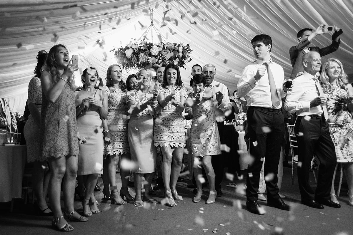 bridesmaids fire confetti cannons during the first dance