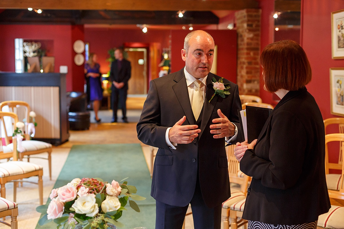 the groom talks with the registrar at brasteds
