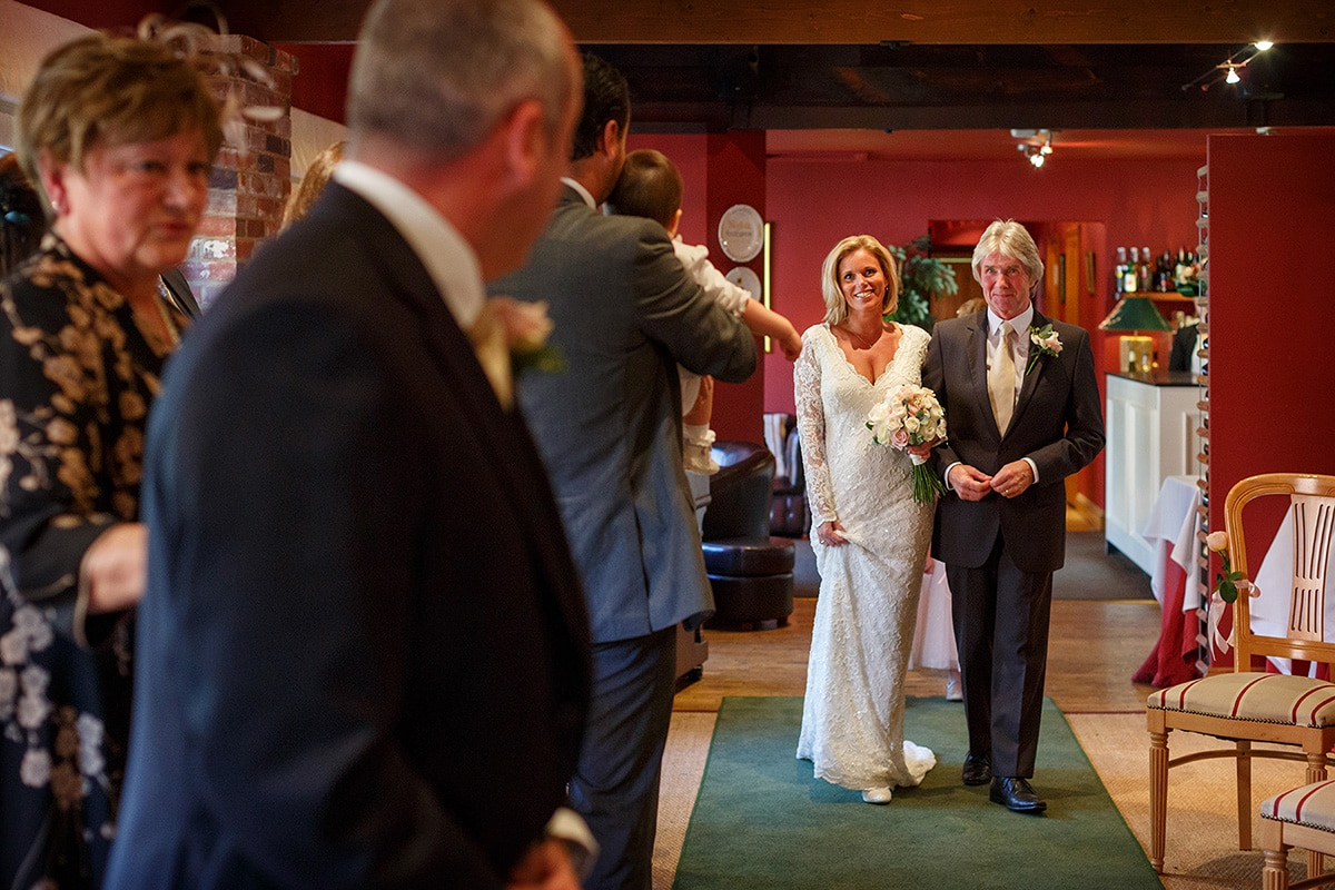 the bride and her father walk down the aisle at brasteds