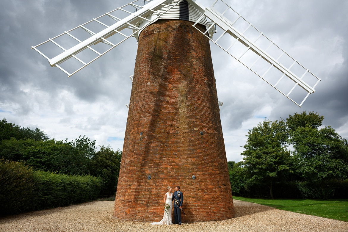 bride and groom pose in fron of dereham windmill
