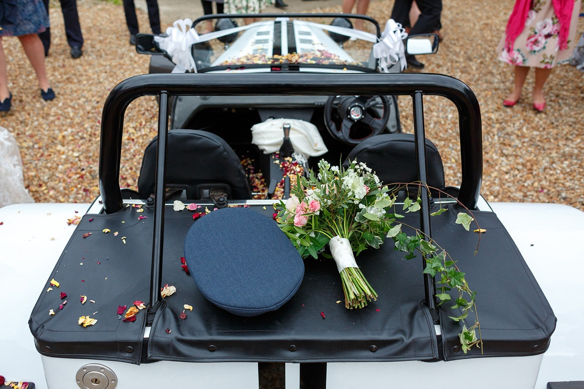 flowers and the grooms hat on the car