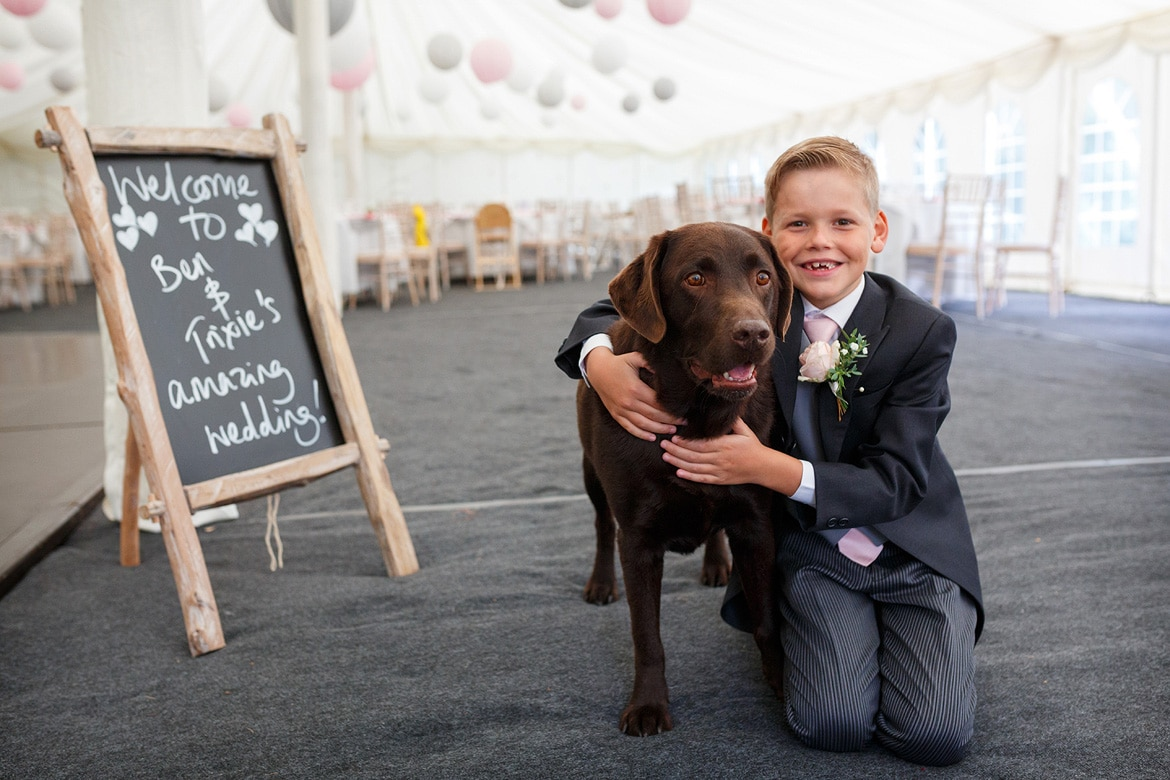 a pageboy hugs the family dog in the marquee