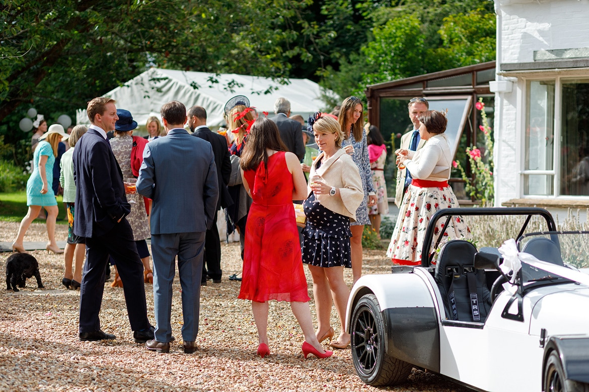wedding guests chat in the driveway