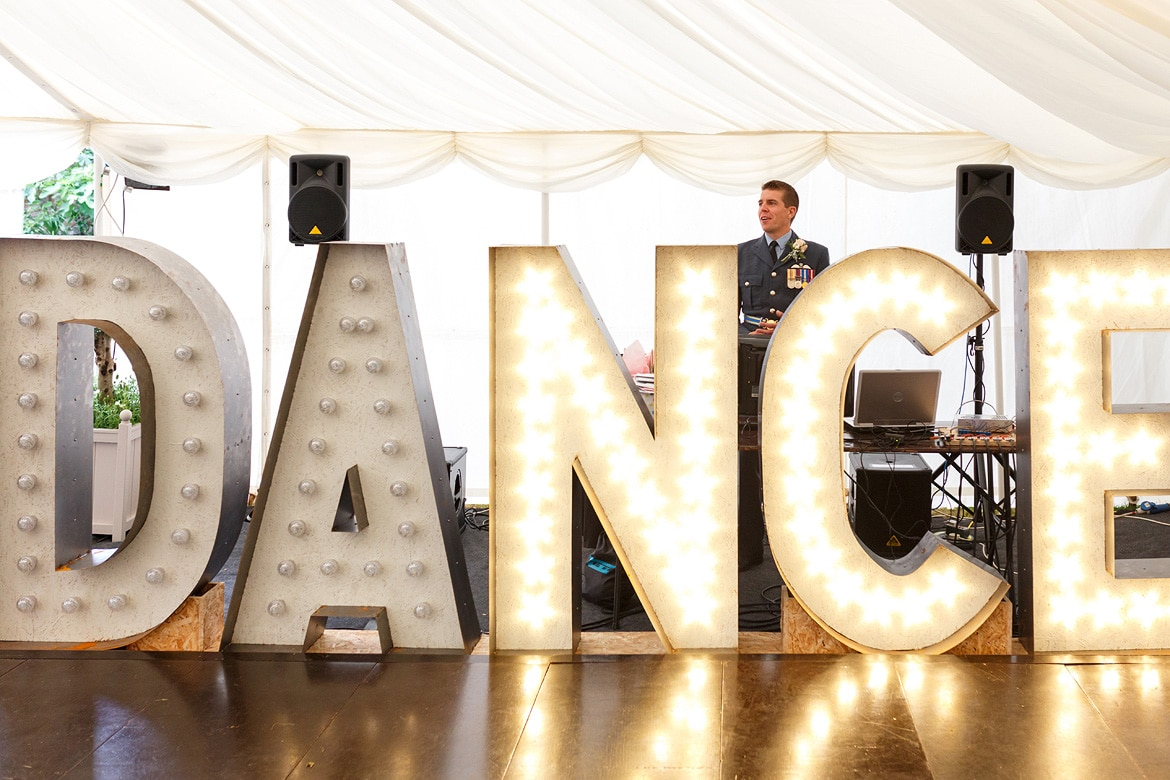the groom stands behind his homemade lighting display
