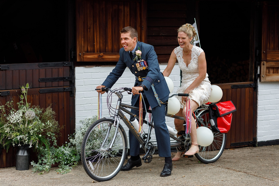 bride and groom on a tandem bicycle