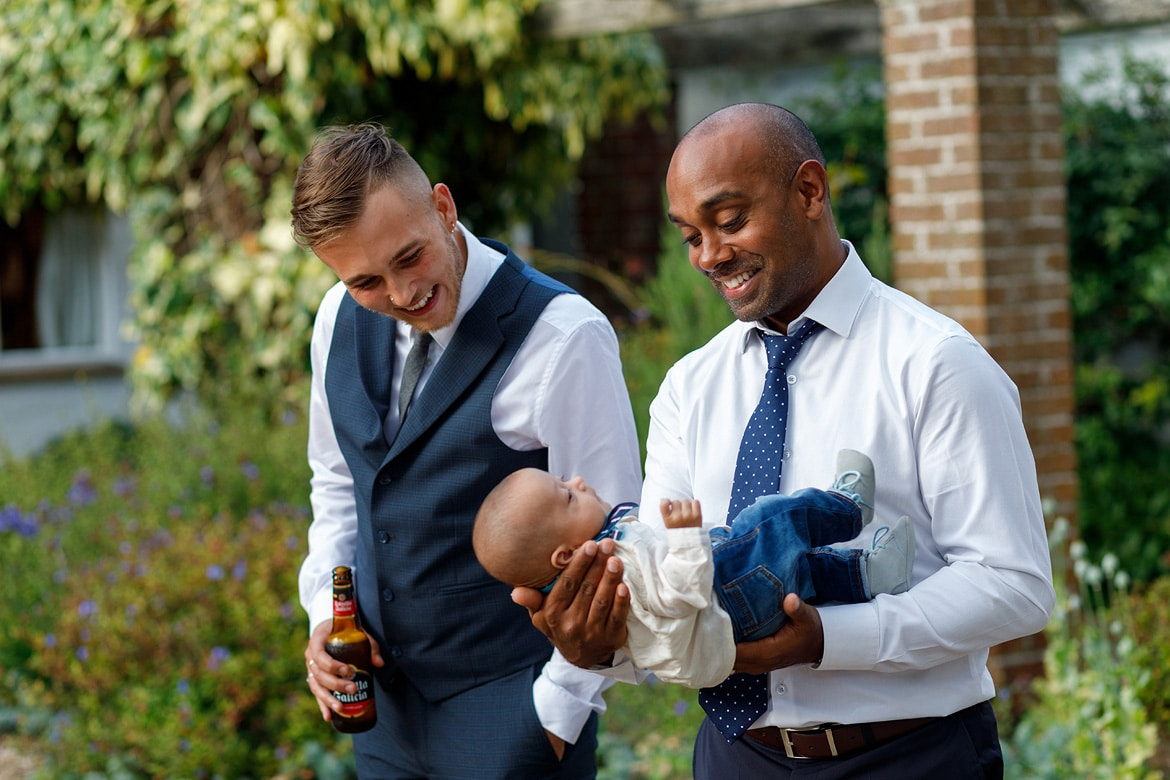 guests play with a baby outside the marquee
