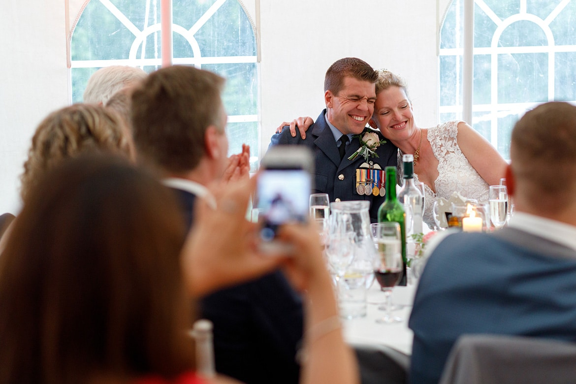 bride and groom embrace at the top table