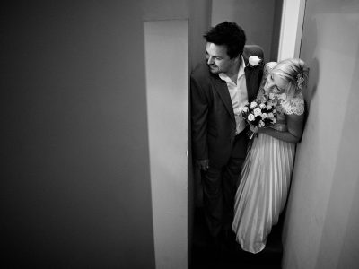 the couple peek into the room before a tuddenham mill wedding ceremony