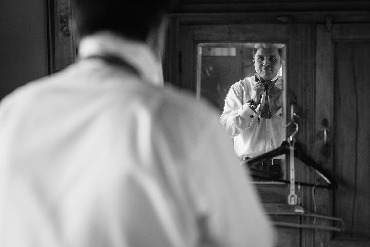 the groom adjusts his tie in the mirror