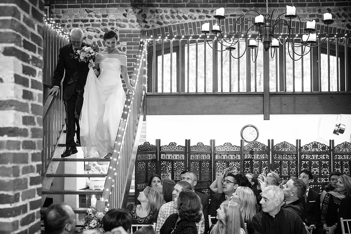 the bride and her father walk down the stairs in chaucer barn