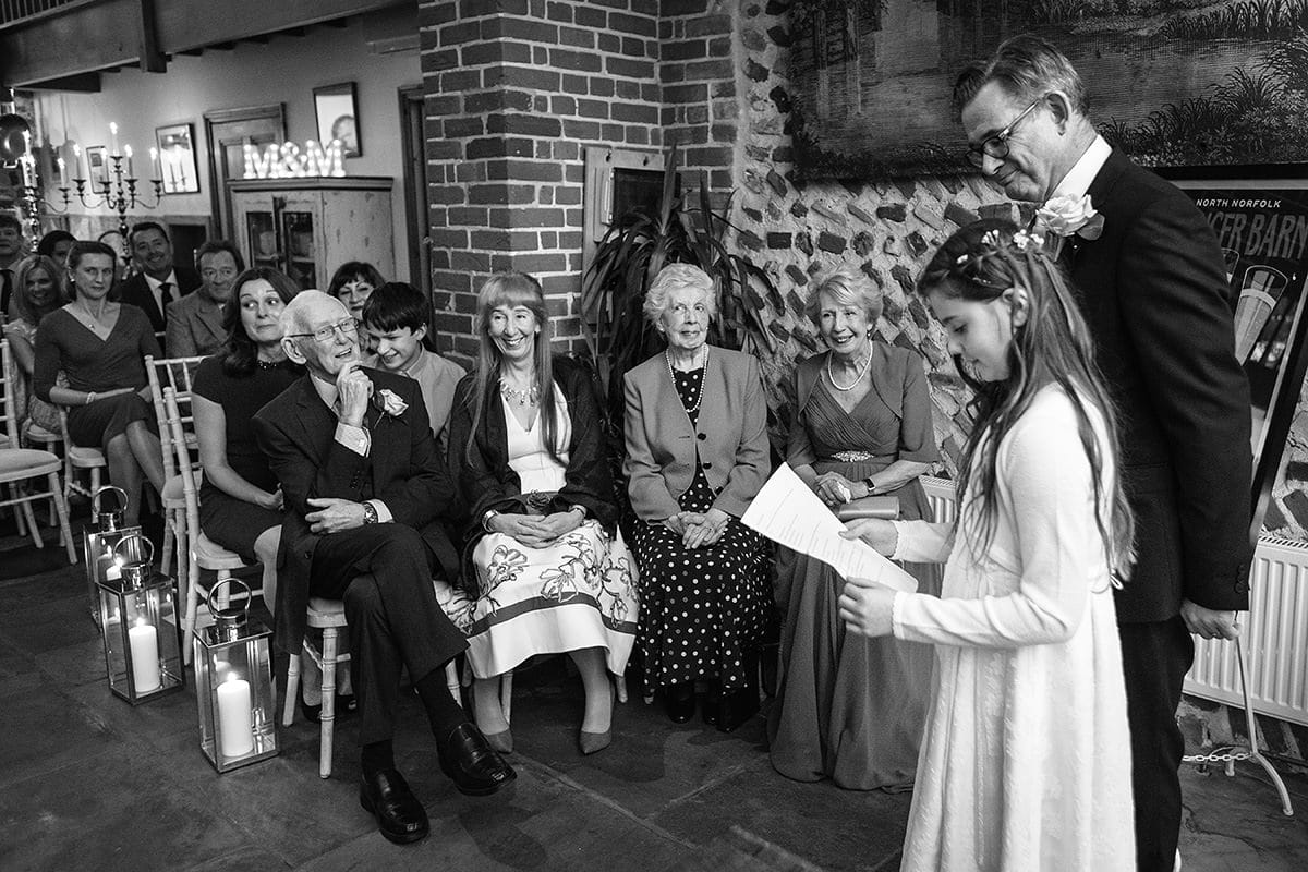 the flowergirl reads during a chaucer barn wedding ceremony