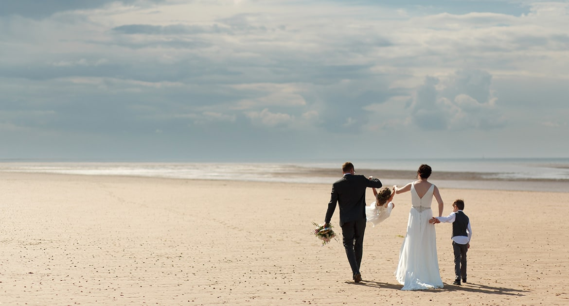 family on brancaster beach after a north norfolk wedding