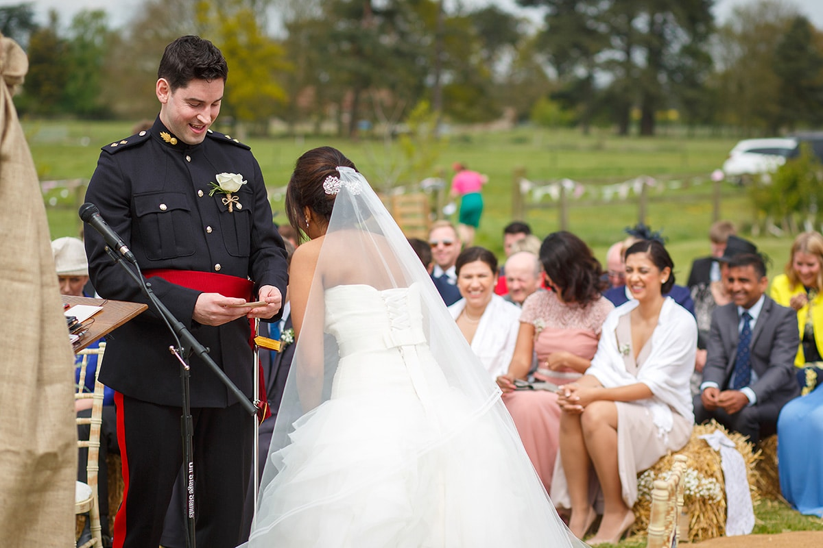 the bride laughs as the groom reads his vows