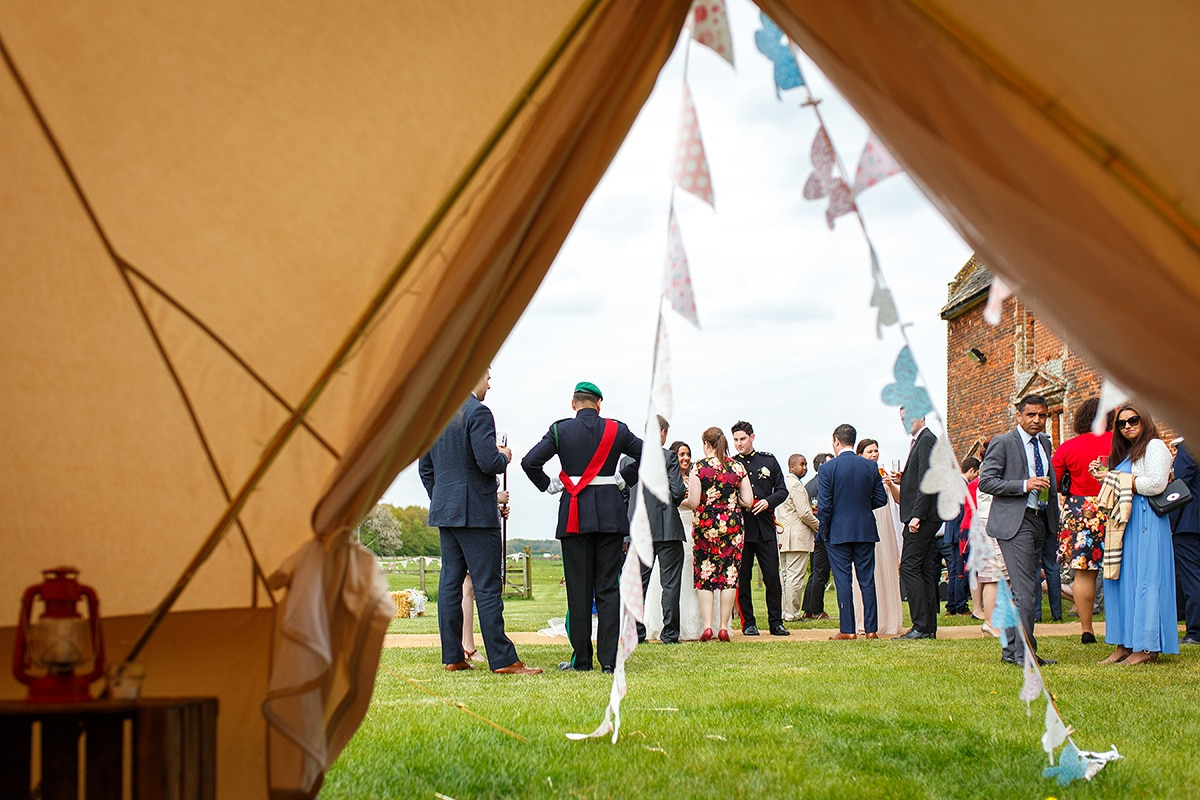 wedding guests viewed from inside the bell tent