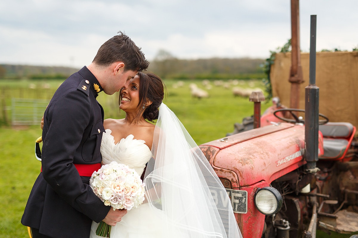 a portrait of the bride and groom with the tractor