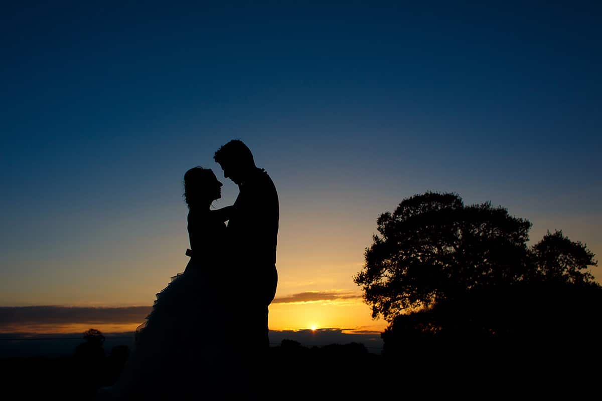a sunset silhouette of the bride and groom at their godwick barn wedding