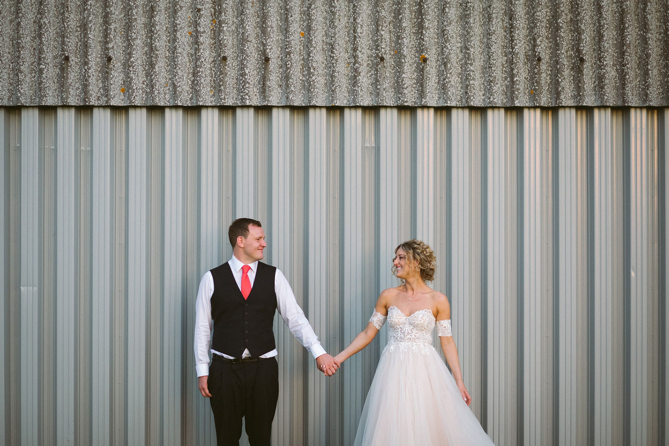 bride and groom pose against a barn
