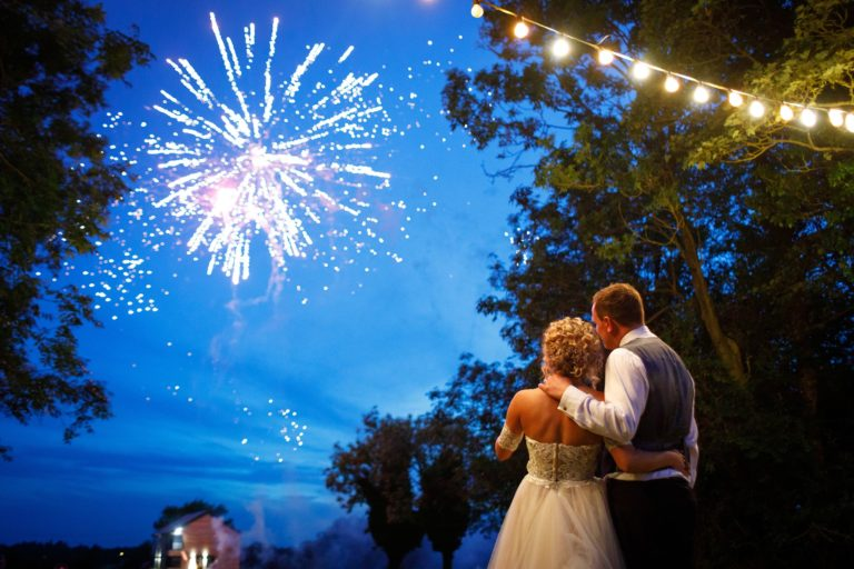 bride and groom watch their wedding fireworks