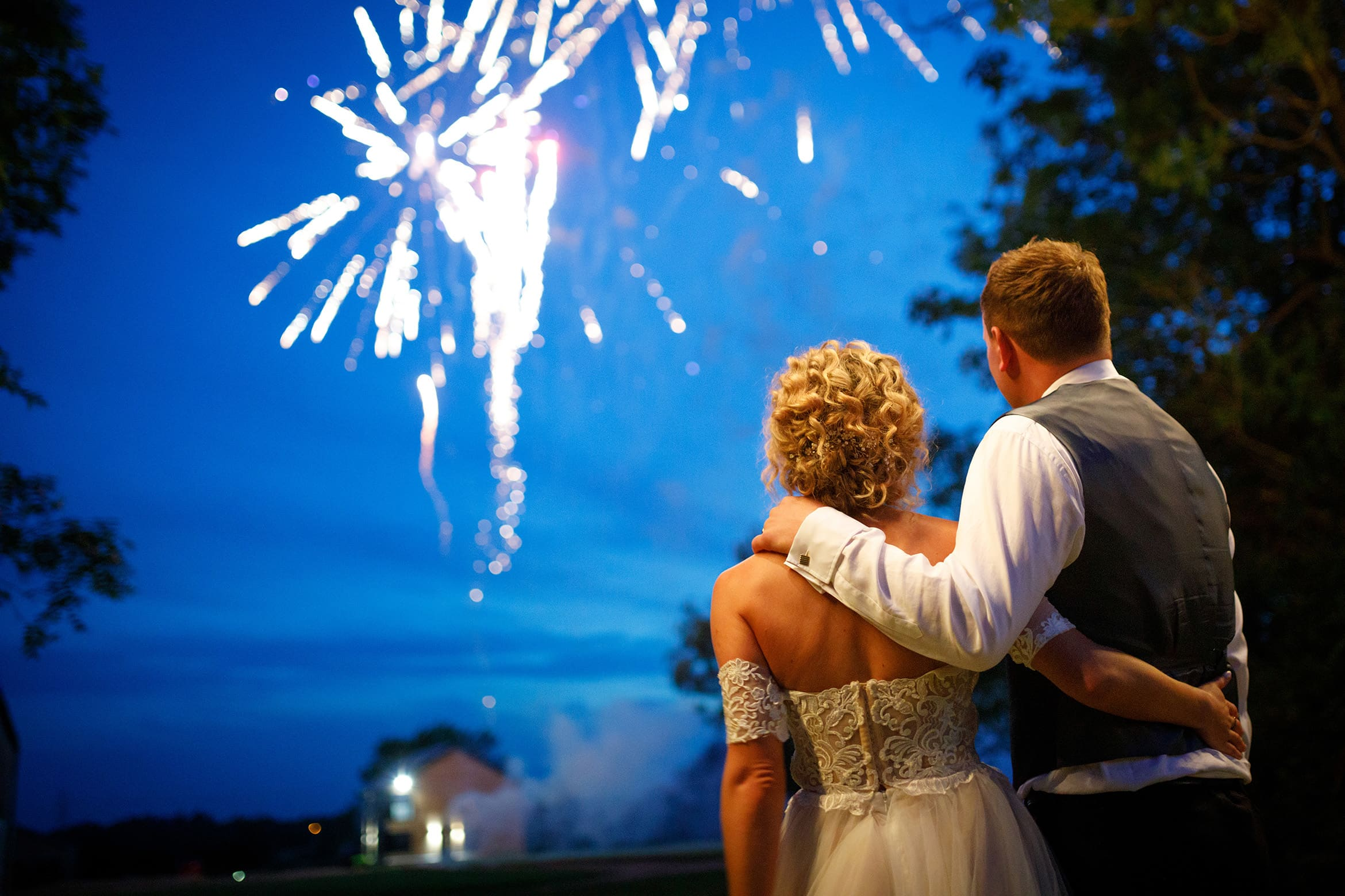 bride and groom embrace in front of the fireworks