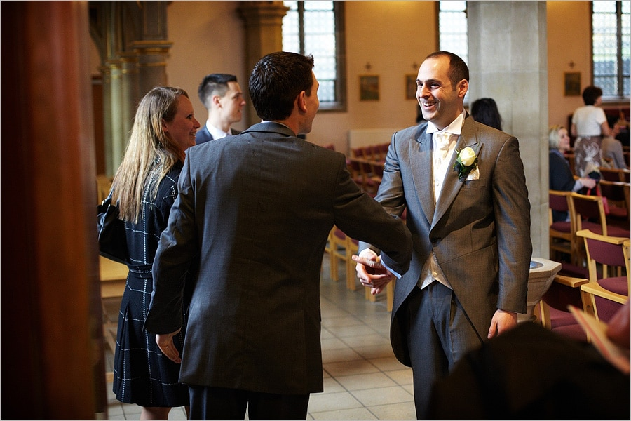 groom greeting guests at the church