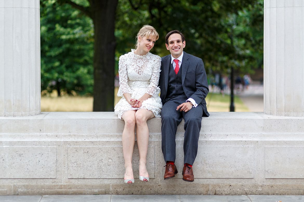 the happy couple sitting on a wall