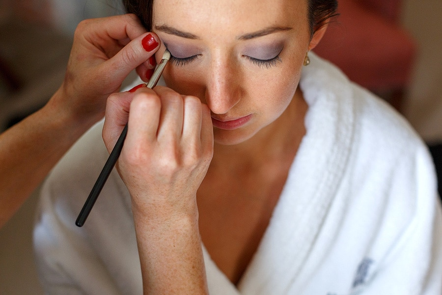 the bride has her makeup applied