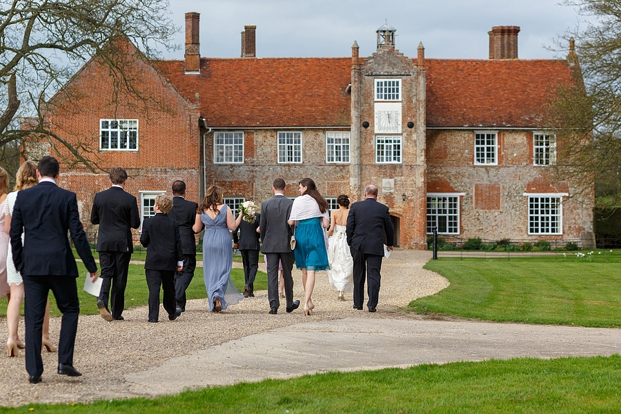 wedding guests walk towards bruisyard hall for the drinks reception