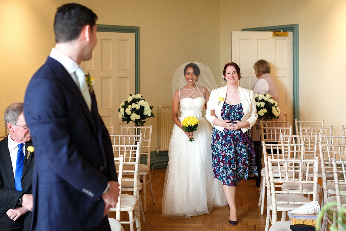 sam walks smiling down the aisle with her maid of honour