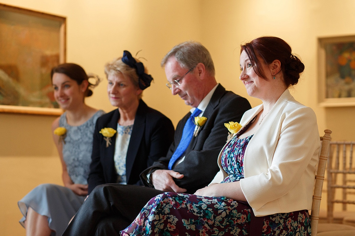smiling wedding guests as sam and rob sign the marriage register