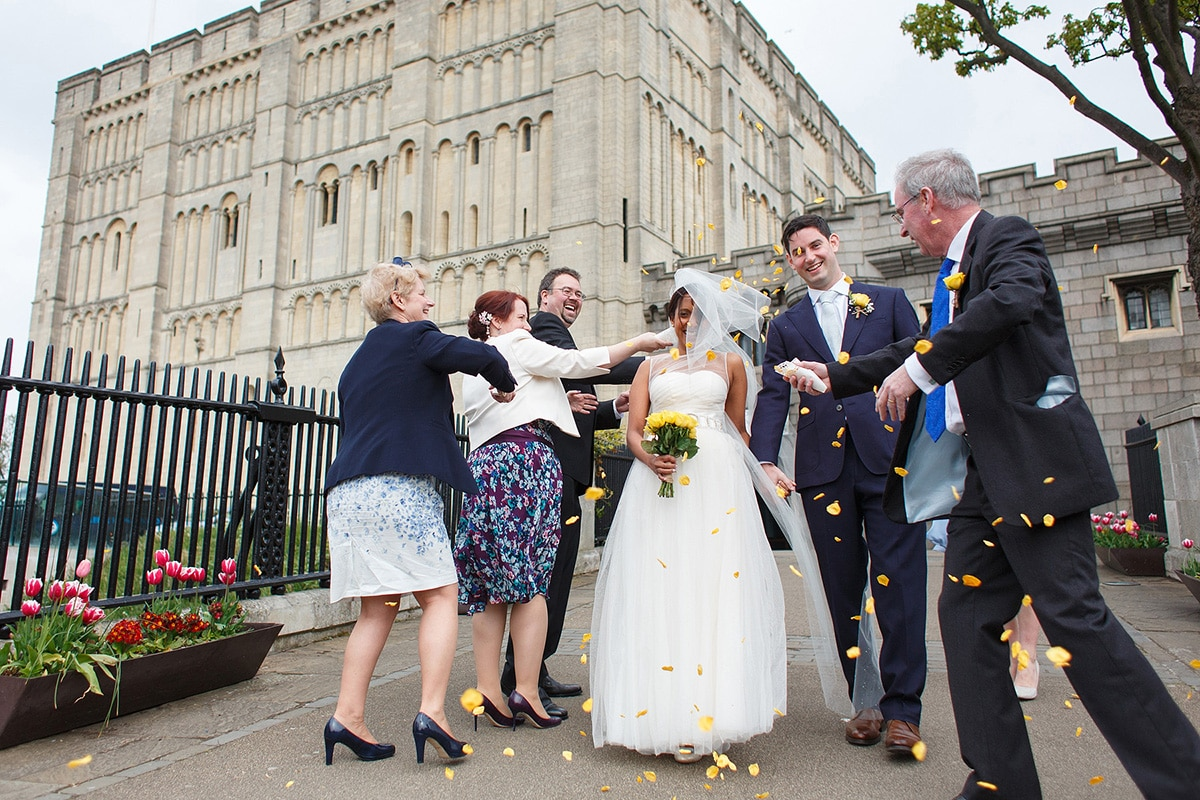 guests throw confetti over the couple outside norwich castle
