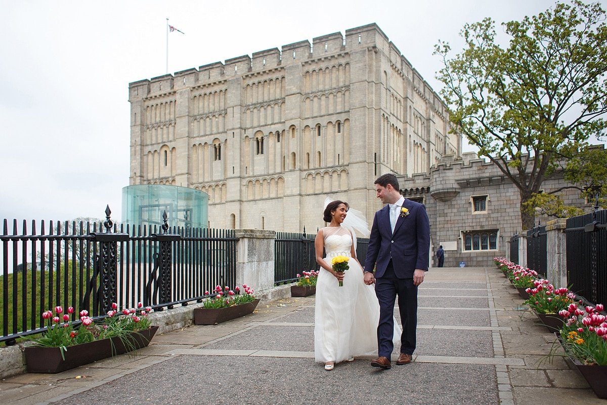 bride and groom walk hand in hand in front of norwich castle