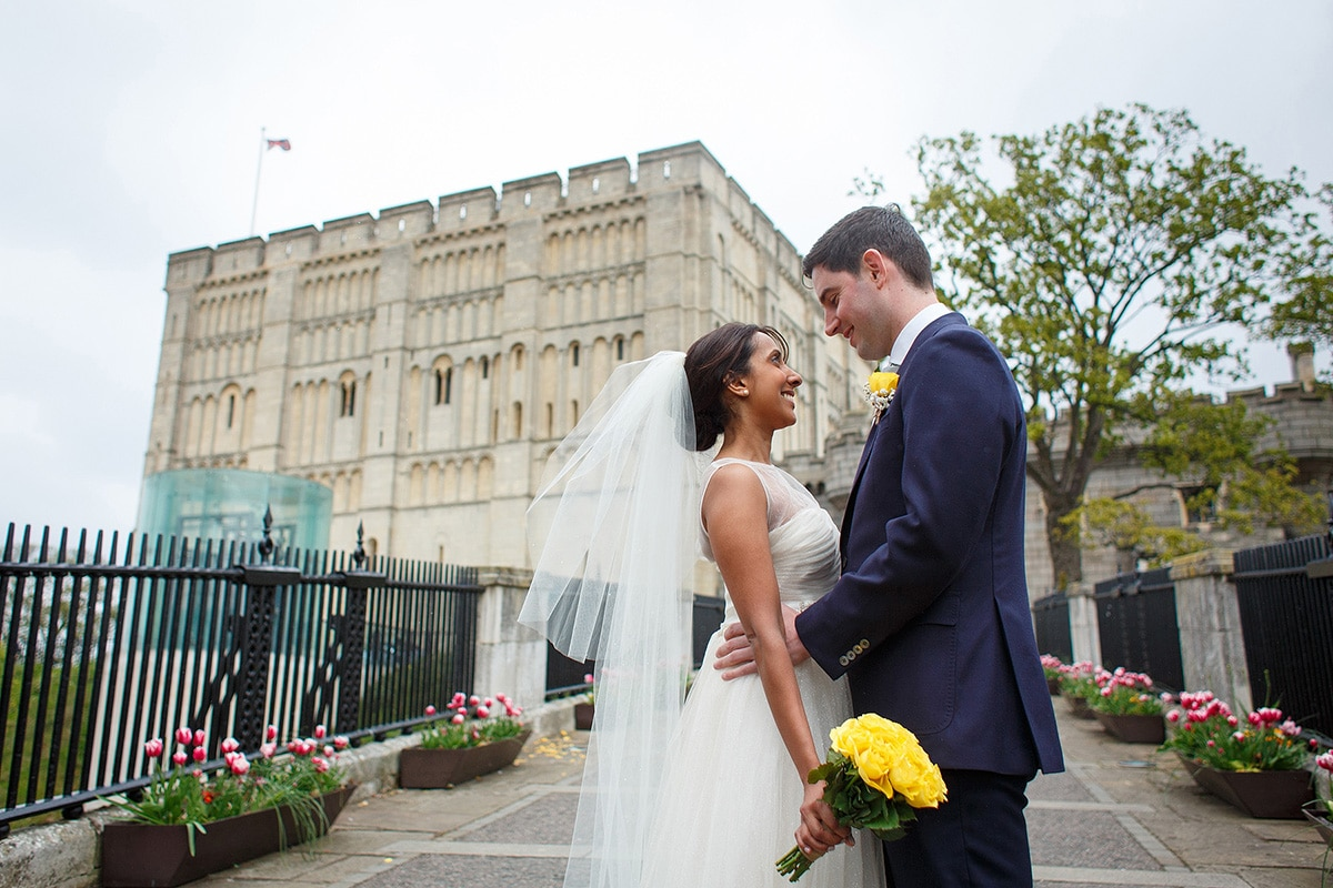 bride and groom gaze into each others eyes in front of norwich castle
